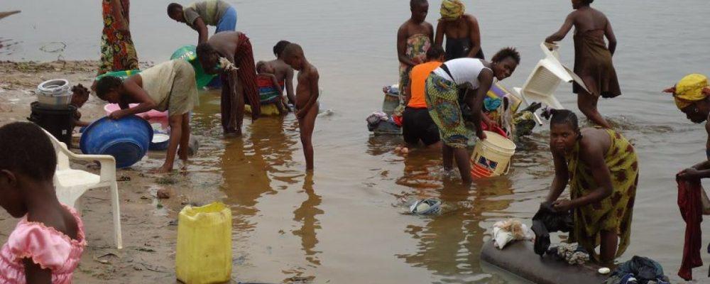 Gente lavando ropa en un río
