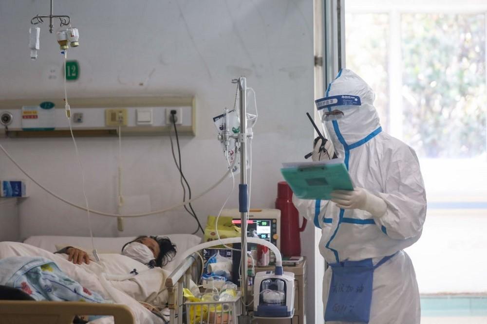 Médico atendiendo a un paciente con el debido equipamiento