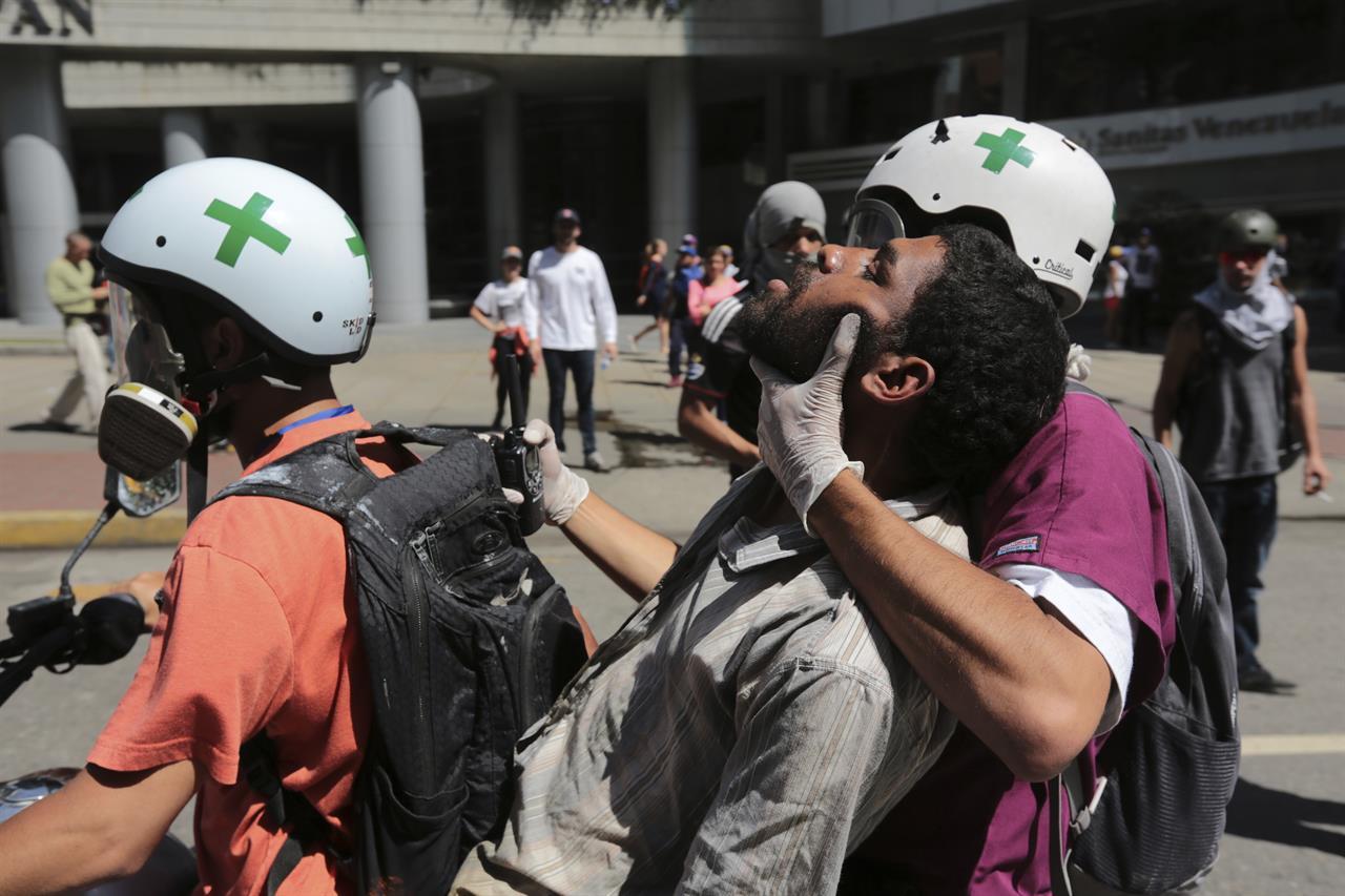 Hombre recibe primeros auxilios por voluntarios en medio de una protesta
